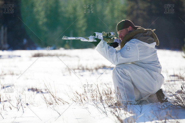 A man wearing a cold-weather camouflage outfit aims a rifle while hunting in a snow-covered field