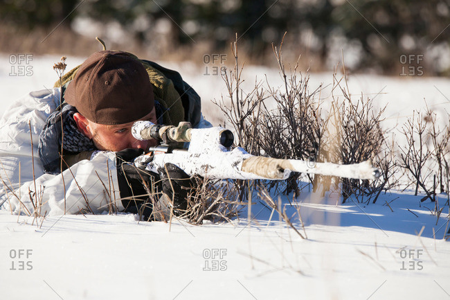 A hunter wearing a cold-weather camouflage outfit aims a rifle at his target while laying down in a snow-covered field
