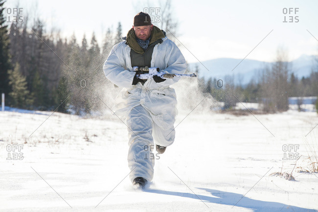 A hunter wearing a cold-weather camouflage outfit carries his rifle while running through a snow-covered field