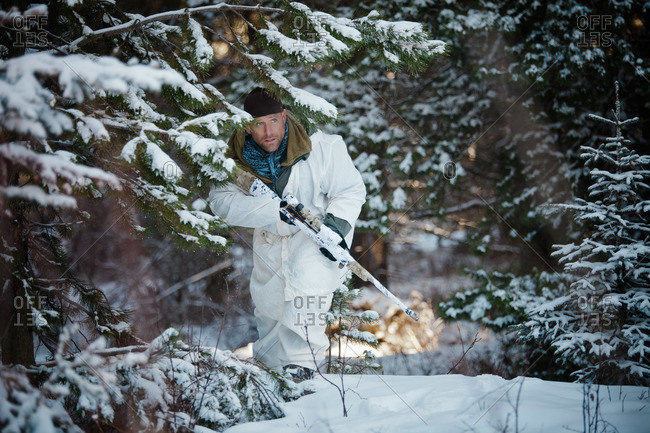 A man wearing a cold-weather camouflage outfit carefully moves through the forest towards his target