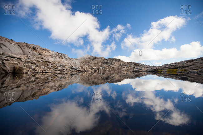 Clouds and blue sky reflected in an alpine tarn