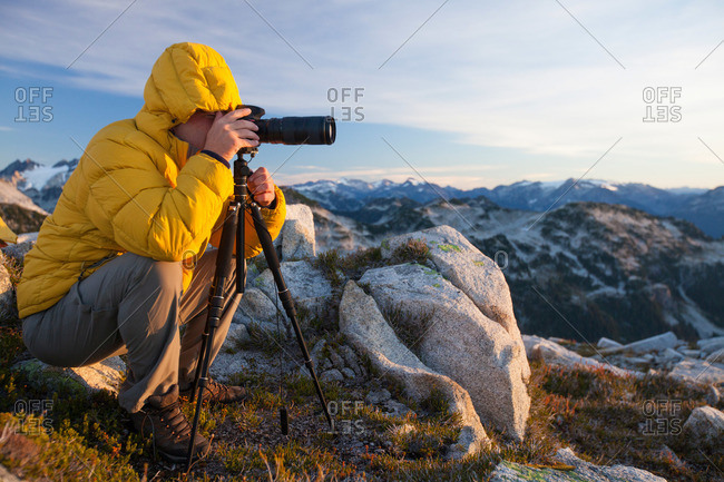 A photographer uses a tripod and a zoom lens to capture a landscape photo from the top of a rocky mountain ridge