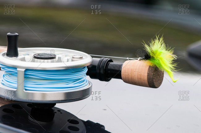 Saltwater reel, rod and fly sitting on top of a car ready for fly fishing