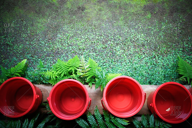 Top view of four red plastic buckets in a row.