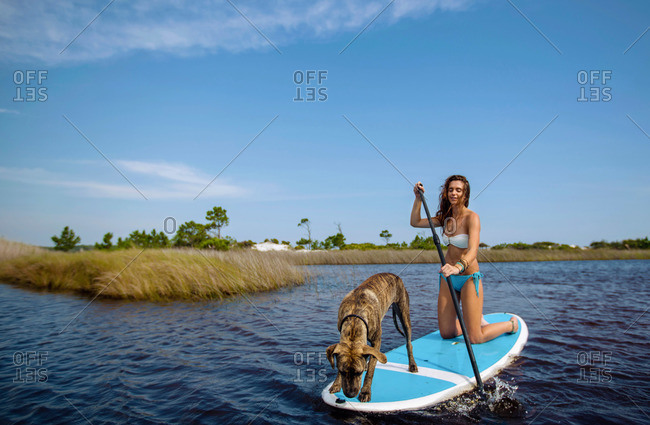 A young woman and her dog ride a stand up paddleboard on a lake in Grayson Beach Florida.