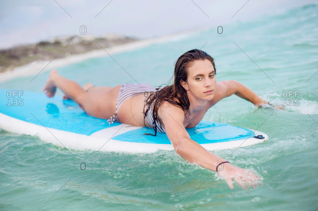 A young woman paddles a board in the waters of the Gulf of Mexico.