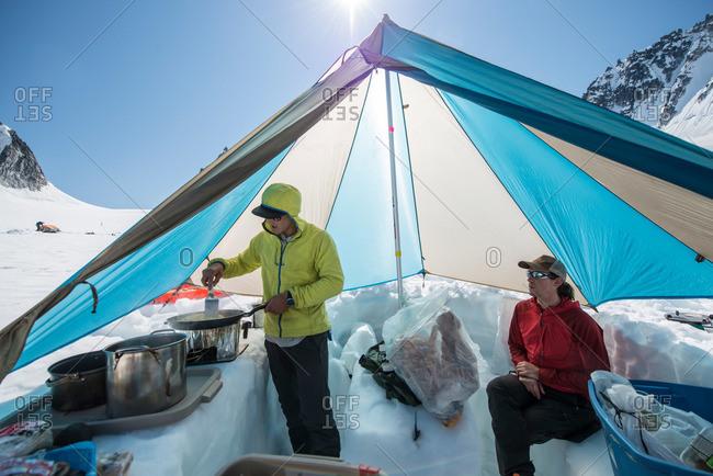 A man makes breakfast in a cook tent on a Glacier in Little Switzerland in the Alaska Range