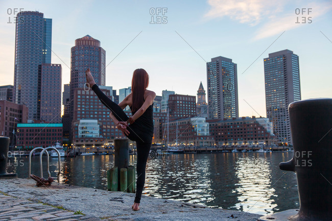 Woman doing Bird of Paradise yoga pose on Boston Harbor in the evening at sunset.