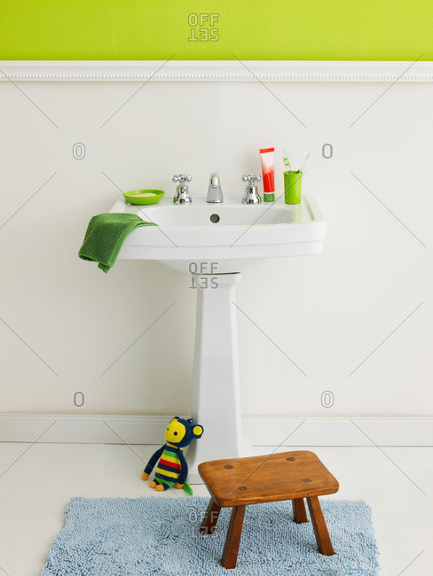 Child's stool and toothbrushes at a bathroom sink