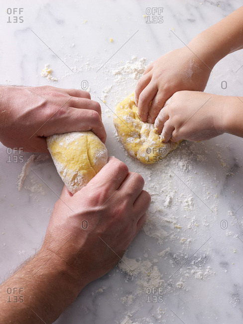 Man and boy kneading pasta dough