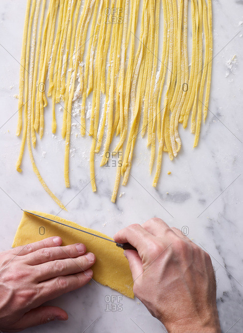 Man cutting pasta from fresh dough