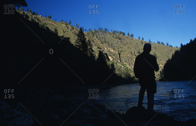 Man overlooking a stream in shadow