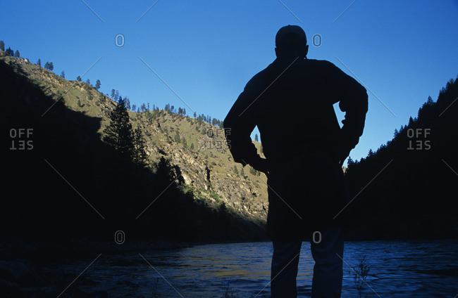 Man looking at a mountain river in shade