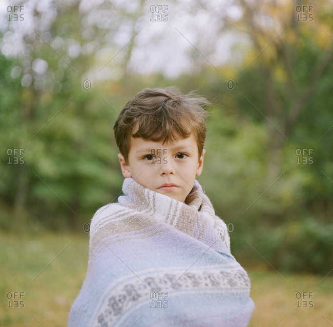 Little boy wrapped in a blanket on a chilly fall day