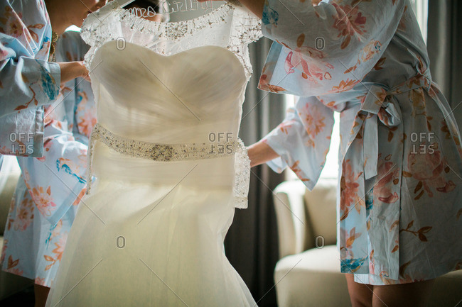 Bridesmaids helping with the wedding gown