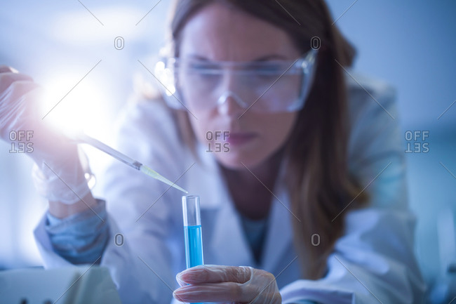 Scientist syringing chemical into test tube at the university