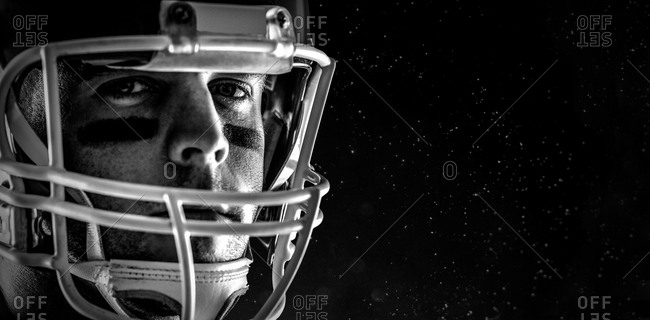 American football player looking at camera against black background