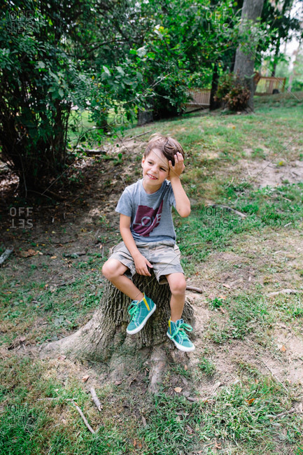 Boy resting on a tree stump in a backyard