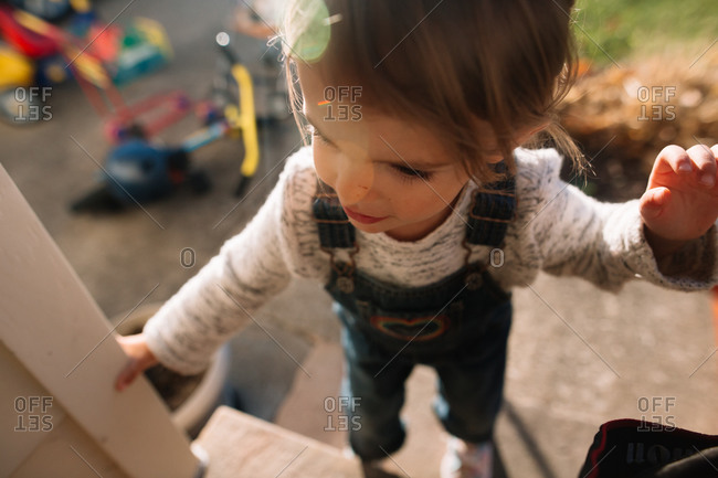 Girl climbing up front steps of her home
