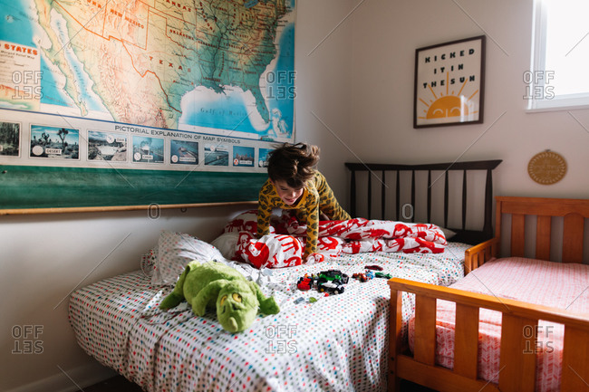 Boy playing with toys on his bed in the morning