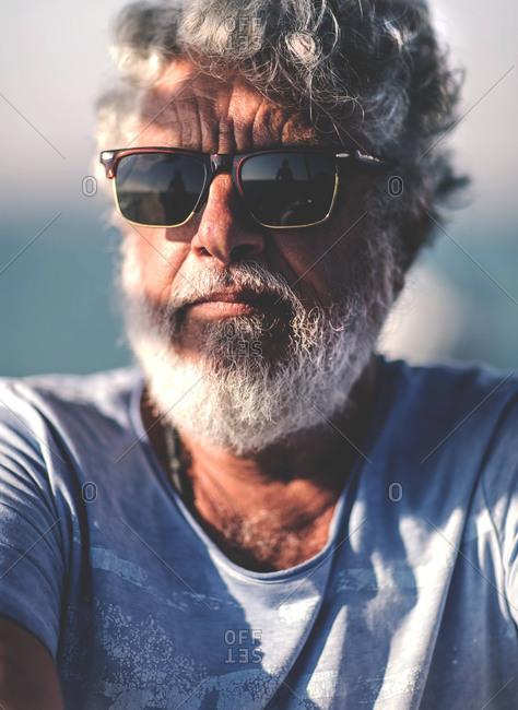 Bearded retired man wearing sunglasses