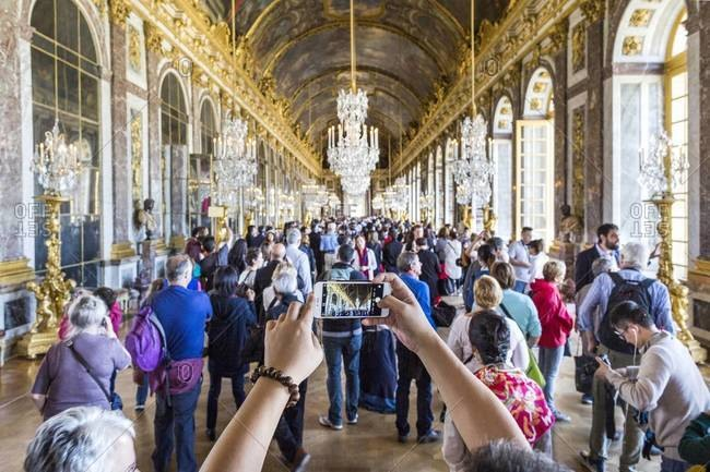 Versailles, France - September 20, 2015: Tourists with camera phone in the Palace of Versailles' Hall of Mirrors
