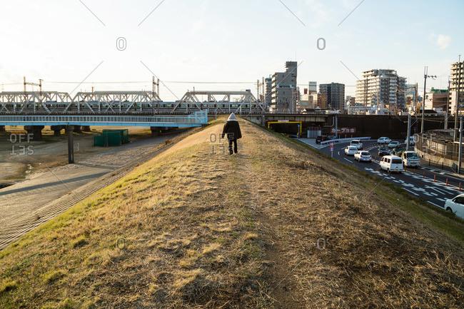 Girl walking near train tracks and highway in Osaka, Japan