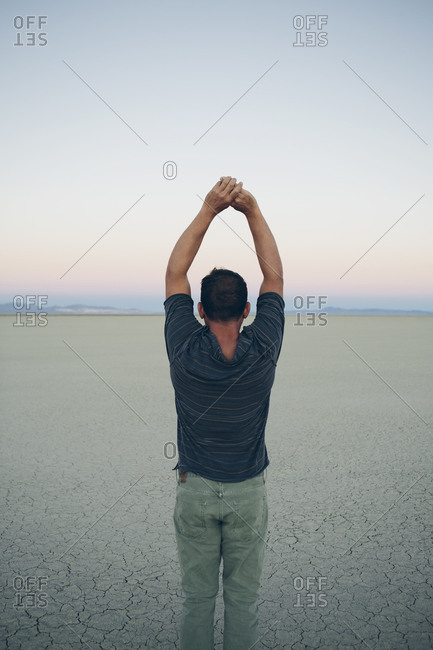 Man stretching with arms above head, facing the sunrise over expansive desert, Black Rock Desert, Nevada