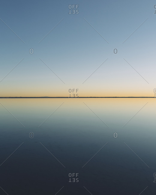 The view to the clear line of the horizon where land meets sky, across the flooded surface of Bonneville Salt Flats Dawn light,