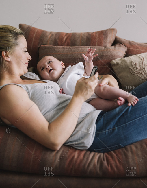 A woman lying on a sofa holding a baby girl, and holding a smart phone in one hand