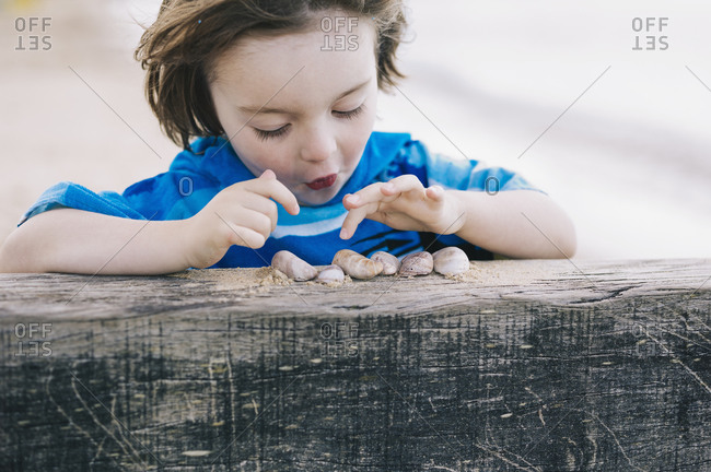 A boy at the beach counting shells lined up on a breakwater