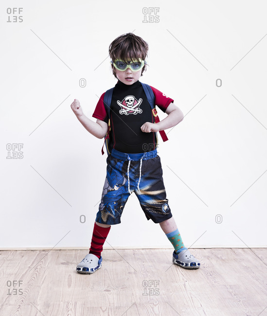 A boy standing with his legs apart posing in fancy dress, wearing a pirate t-shirt, eye goggles and long shorts