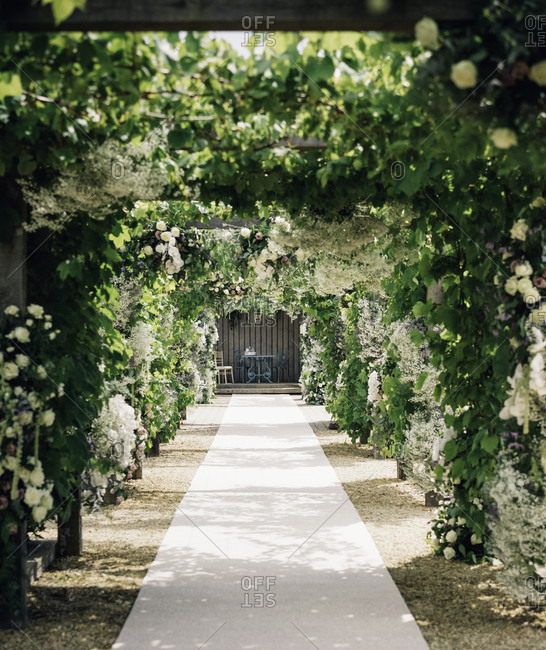 A garden path under a pallisade leading to an alcove with table and chairs, with climbing plants and white roses