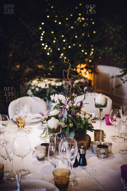 A table laid for a special occasion, with a floral centerpiece and candles, at night