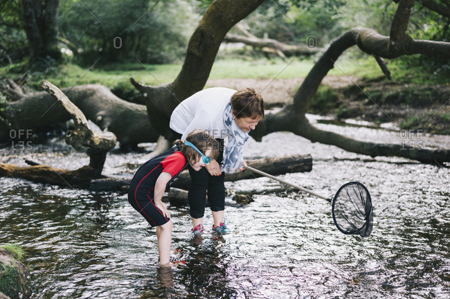 A woman giving a boy a piggyback and holding a shrimping net wading in a shallow stream