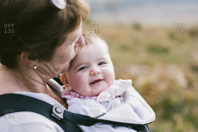 A woman carrying a baby in a baby carrier, kissing her on the head