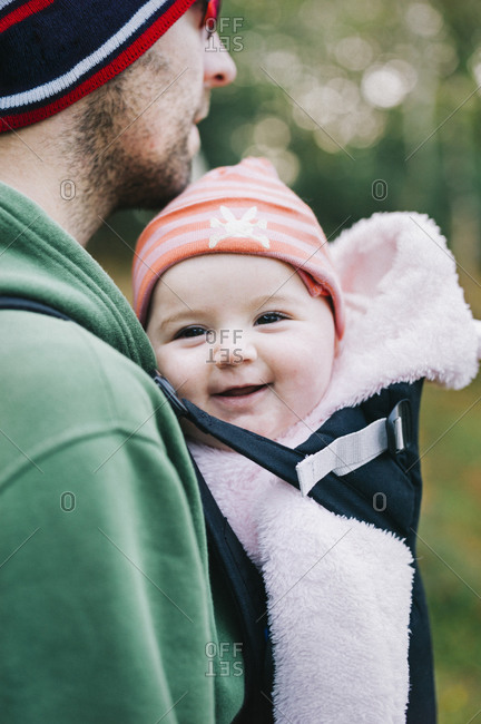 A baby in a sling being carried by her father, outdoors in winter