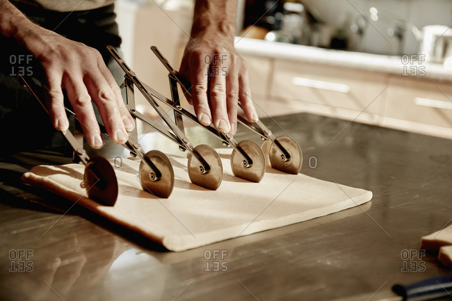 A baker working on a floured surface, dividing the prepared dough into squares using an expandable rotary dough cutter