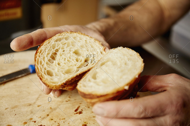 A man holding a croissant cut in half, to show the light layered texture of the cooked dough