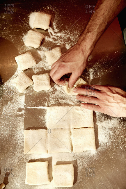A baker folding dough squares on a floured surface