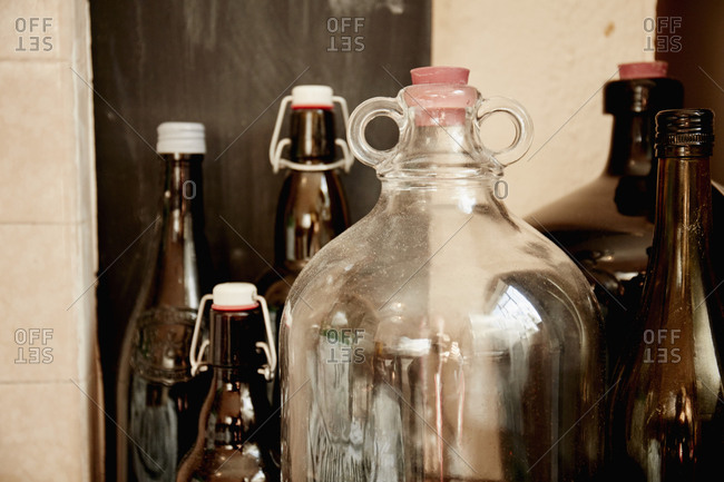 A shelf of bottles and jars, one large double handled jar with a stopper and bottles with lids