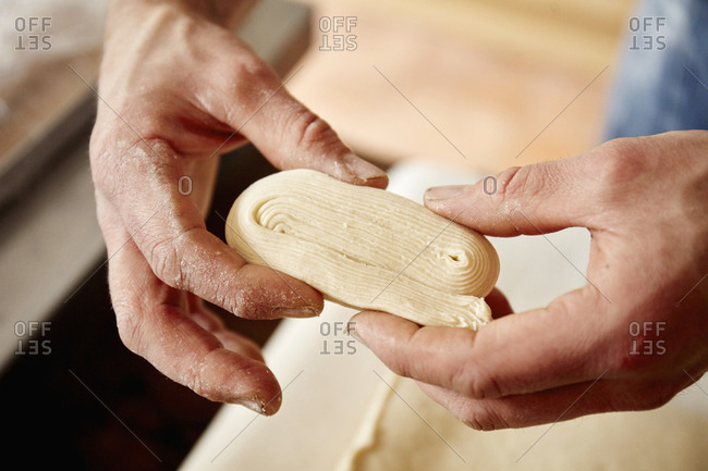 A baker holding dough which has been folded and worked to show the layers incorporated into the dough, to make light layered pastries