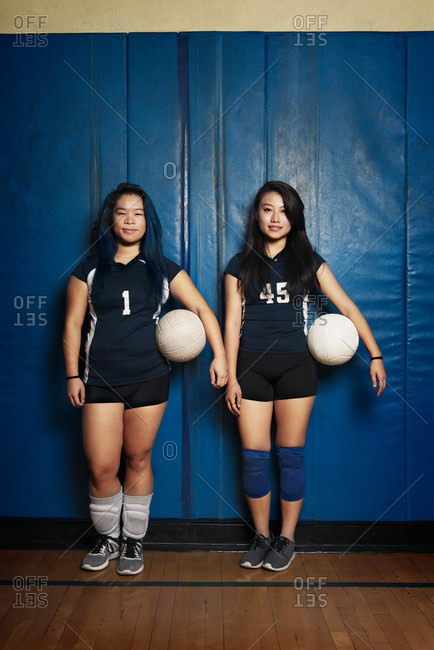 Two female volleyball players holding ball