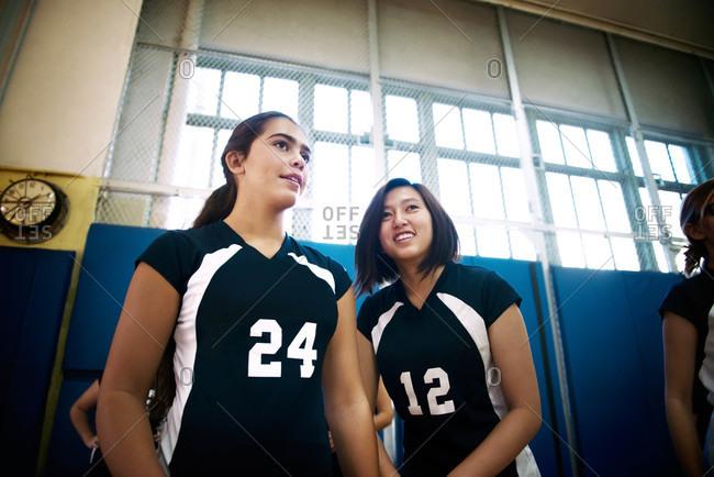 Girls watching teammates play volleyball