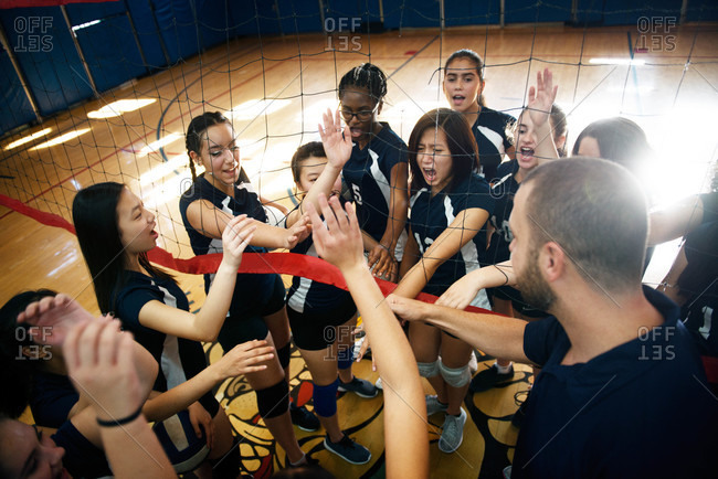Coach and volleyball players in huddle