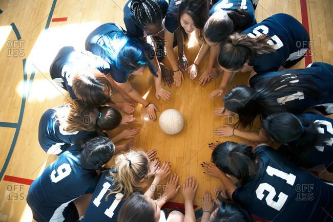 Volleyball players circled around ball
