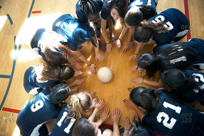 Volleyball players circled around ball