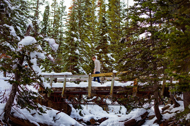 Men crossing bridge in winter wilderness