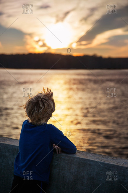 Boy leaning over barrier by rural lake