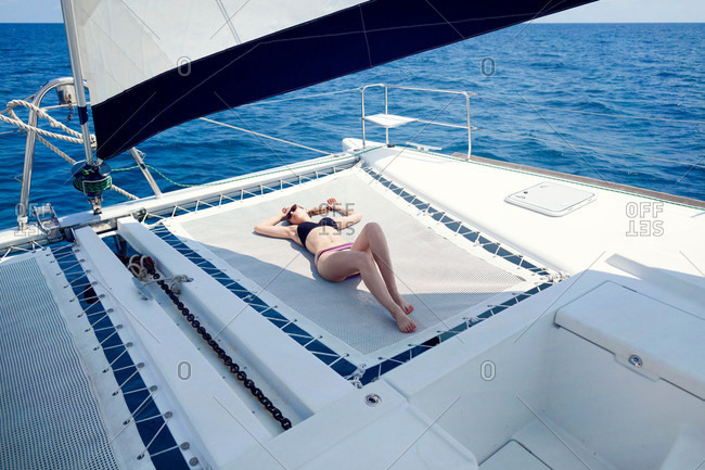 Woman lying on sailboat trampoline
